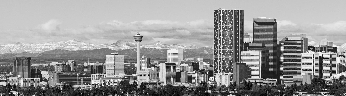 Downtown Calgary city core with large blue mountains far behind it
