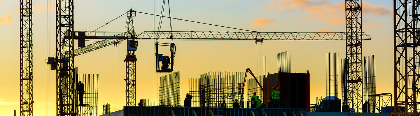 Tower cranes and building silhouette with workers at sunset
