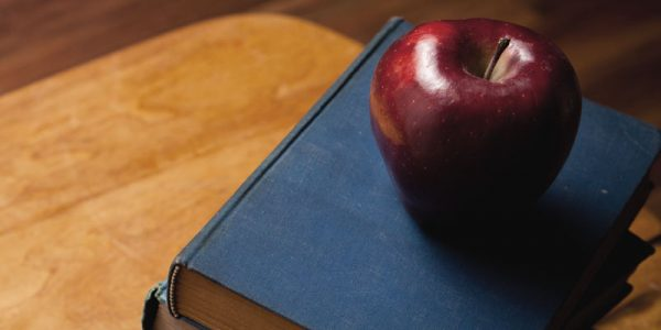 Pile of books on a wooden desk with a red delicious apple on top