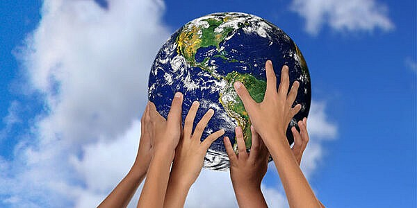 Many hands holding up a globe with a sky background