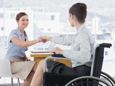 Photo showing businesswoman shaking hands with colleague who has a disability