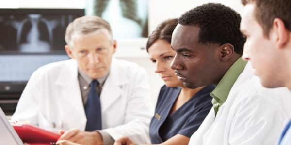 Médecins et personnel médical devant un ordinateur portable