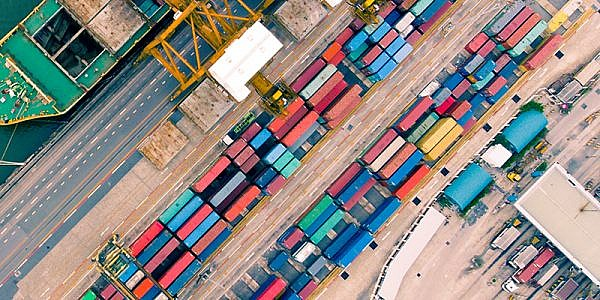 Top view of container ship in export and import business and logistics. Shipping cargo to harbor by crane. Aerial view Container Cargo ship and Cargo plane with working crane bridge in shipyard